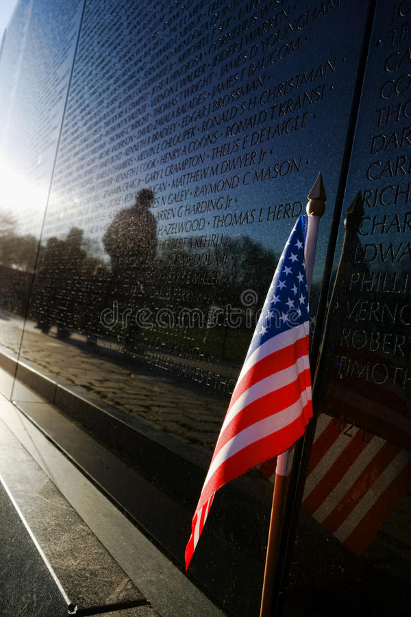 Vietnam Veterans Memorial Wall and American Flag. Small patriotic American flag on Vietnam War Veterans national Memorial wall honoring fallen US soldiers and royalty free stock images