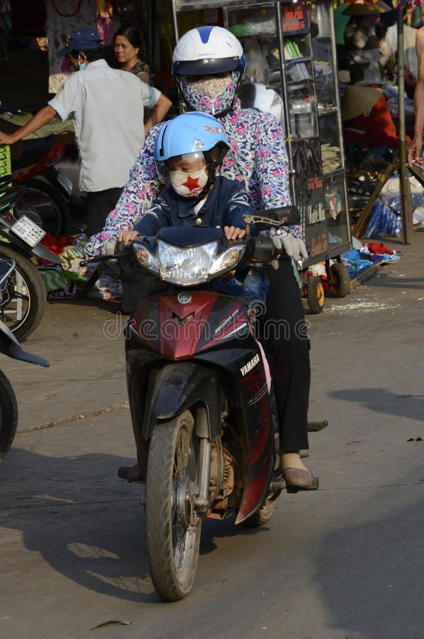 Vietnam Villages on motor bikes with young children. Vietnam young children ride with parents on their motor bikes and are covered to protect from pollution and stock images