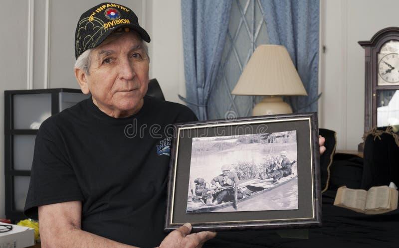 Vietnam war veteran holds an old war photo of himself. stock photo