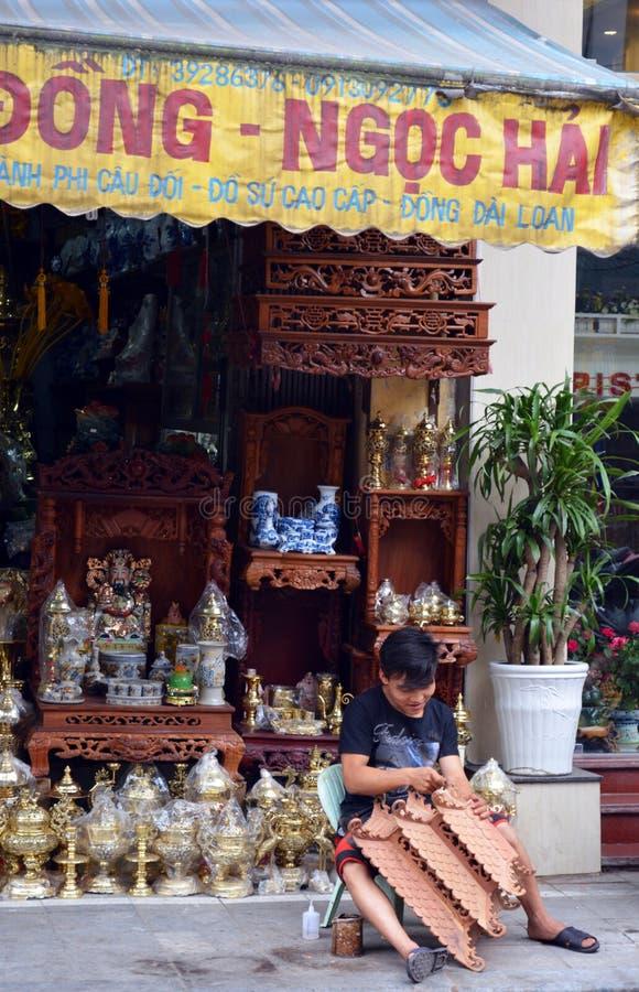 Vietname - Hanoi - cena típica do quarto velho - vendedor ambulante da rua que cinzela a estátua imagem de stock