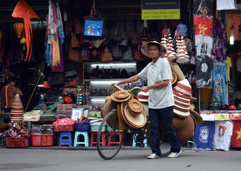 Vietname - Hanoi - cena típica do quarto velho - vendedor ambulante da rua que vende chapéus do peão fotografia de stock royalty free