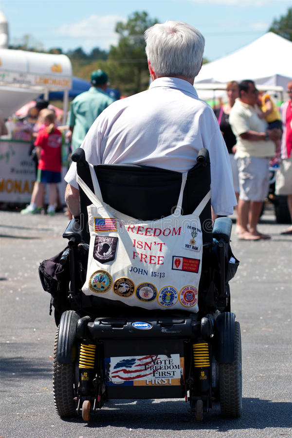 Vietname Veteran Amputee In Wheelchair. CONYERS, GA - MARCH 24: An unidentified Vietnam War veteran uses a motorized wheelchair to get around the Cherry Blossom stock photos