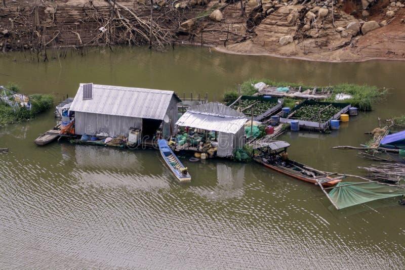 Vietnamees die visserijdorp op het water op Meergebrek wordt voortgebouwd in de bergen stock foto