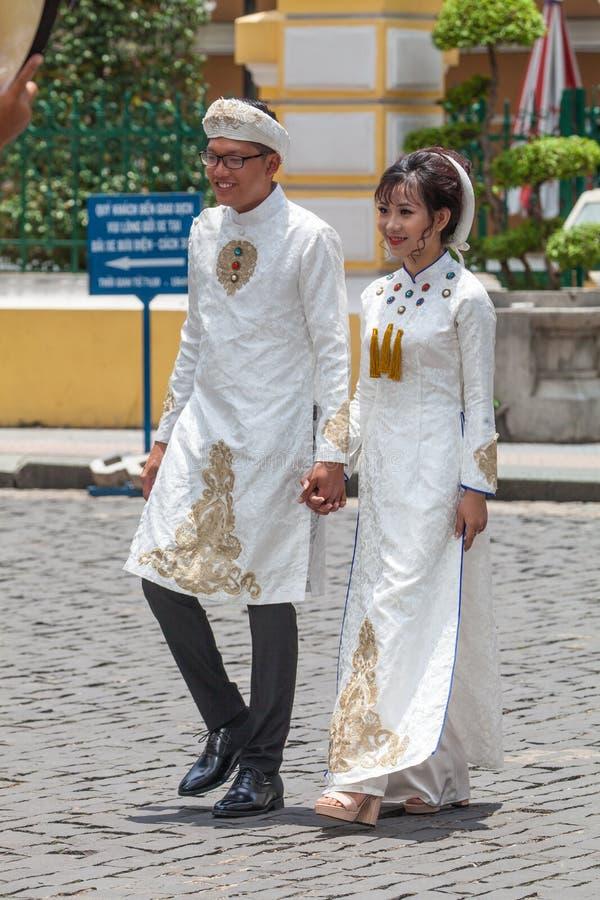 Vietnamees echtpaar die in witte kleding op de straten lopen stock fotografie