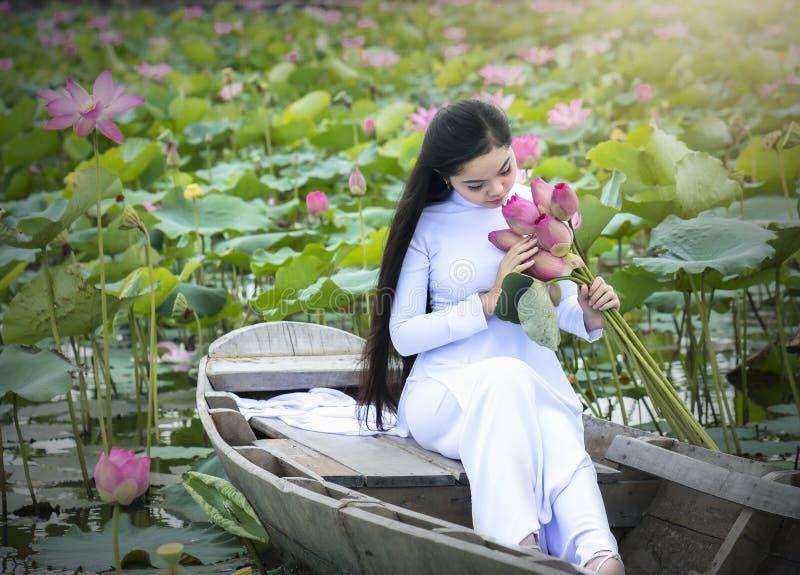 Vietnamees meisje in traditionele lange kleding of Ao Dai binnen boot stock afbeeldingen