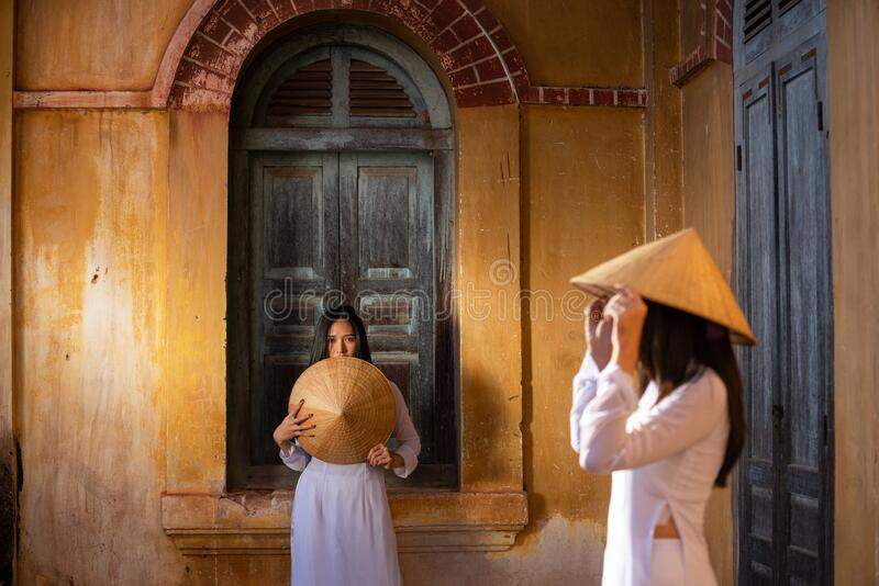 Vietnamese Ao Dai dress portrait concept. In old house stock photo