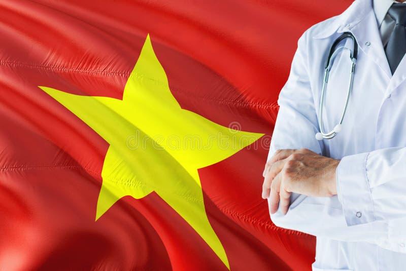 Vietnamese Arts die zich met stethoscoop op de vlagachtergrond van Vietnam bevinden Het nationale concept van het gezondheidszorg stock foto's