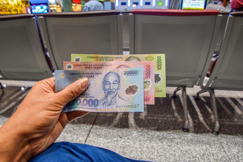 Vietnamese banknotes are in the hands of men in Hanoi airport, Vietnam royalty free stock photo