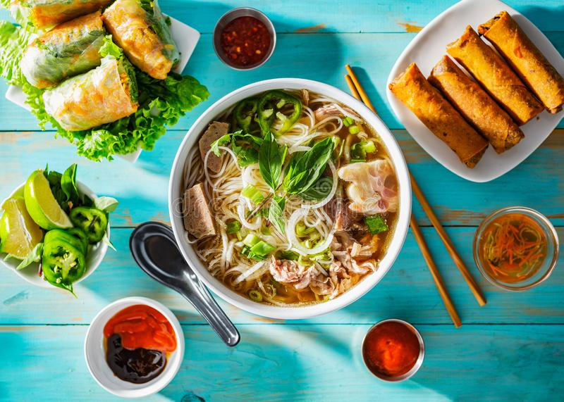 Vietnamese beef pho bo soup in bowl on table top with spring rolls and appetizers stock image