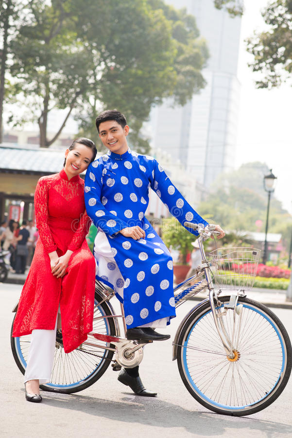 Vietnamese on bicycle. Vietnamese couple posing on bicycle in traditional clothes royalty free stock photo
