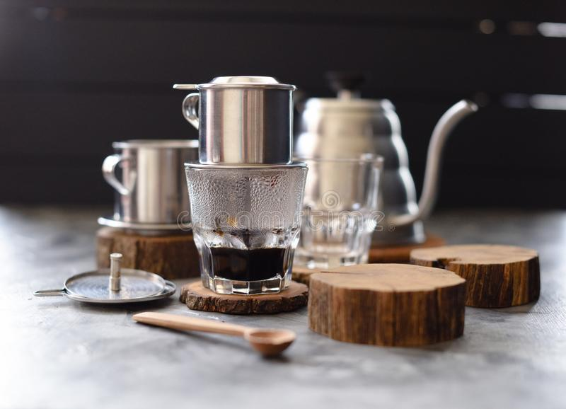 Vietnamese black drip coffee. Traditional Vietnamese coffee maker phin and goose neck kettle on wood slabs on dark background royalty free stock images