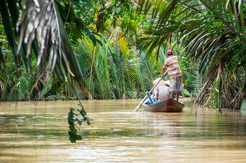 Vietnamese boatman in the Mekong Delta. A Vietnamese boatman on a canal in Ben Tre province in the Mekong Delta region of Vietnam, rowing a traditional wooden royalty free stock images