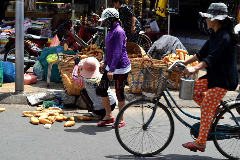 Vietnamese bread saleswoman. Pick up spread bread. Phantiet streetmarket stock image