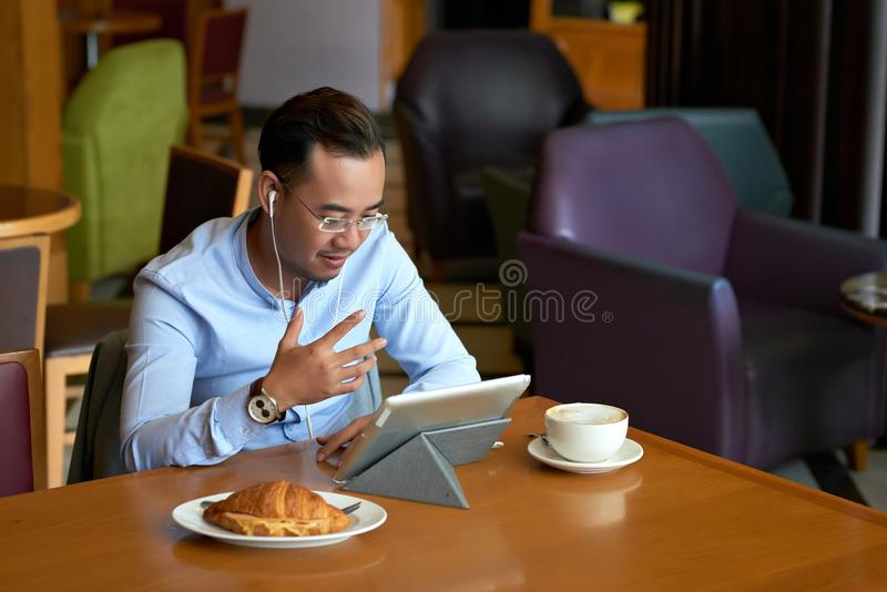 Videocalling. Vietnamese businessman having breakfast and videocalling via digital tablet stock photo