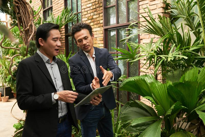Look at this project. Vietnamese businessman showing project on tablet computer to his coworker stock photography