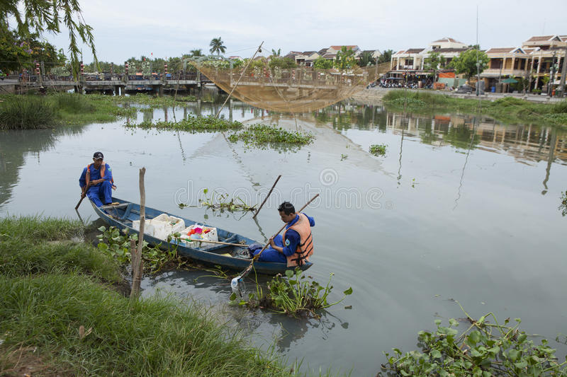 Vietnamese cleaners cleaning Hoai river from wastes stock image