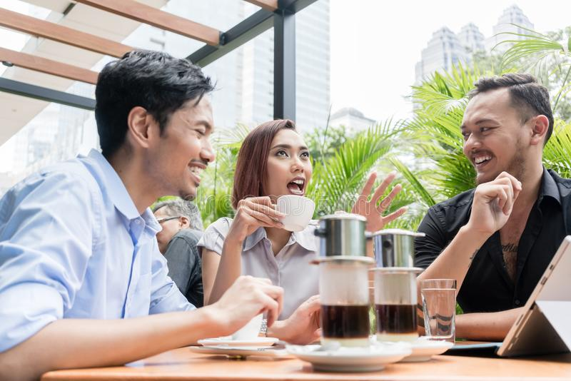 Vietnamese coffee served on the table of three friends outdoors. Delicious Vietnamese coffee served on the table of three young cheerful Asian friends outdoors royalty free stock image