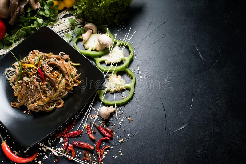 Vietnamese cuisine food rice noodle vegetable beef. Vietnamese cuisine food. traditional meal. rice noodle vegetable beef meat dish on a plate. dark background royalty free stock images