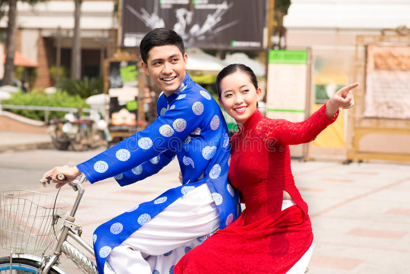 Vietnamese cyclists. Two Vietnamese riding bicycle in traditional clothes royalty free stock image