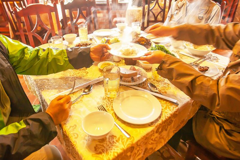 Vietnamese dinner, a vietnamese family seated at the dining room table serving themselves to a steamed rice dinner stock photos