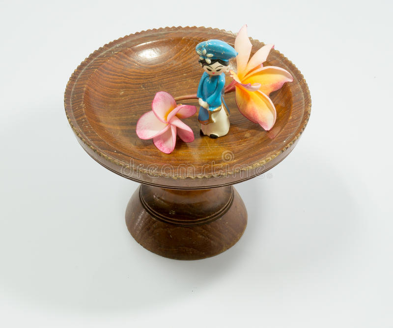 Vietnamese doll and Plumeria flowers on wooden tray. On a white background royalty free stock photography