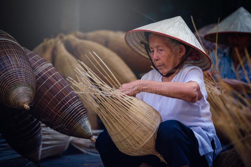 Vietnamese fishermen are doing basketry for fishing equipment at. Morning in Thu Sy Village, Vietnam royalty free stock image