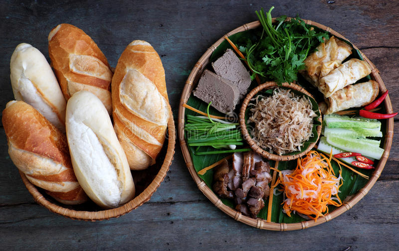Vietnamese food, banh mi thit. Famous Vietnamese food is banh mi thit, popular street food from bread stuffed with raw material: pork, ham, pate, egg and fresh royalty free stock photography