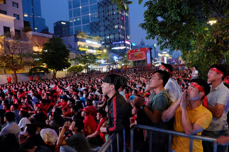Vietnamese football fans watching match on outdoor lcd screen. HO CHI MINH CITY, VIET NAM- JAN 27, 2018: Group of Vietnamese football fans sit and watching match stock image