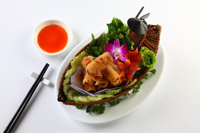 Vietnamese fried spring rolls on bamboo tray with sliced cucumber, salad and chili sauce stock photos