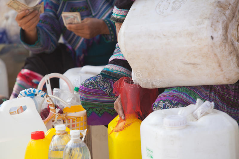 Vietnamese Hmong women selling traditional wine in canes royalty free stock photography