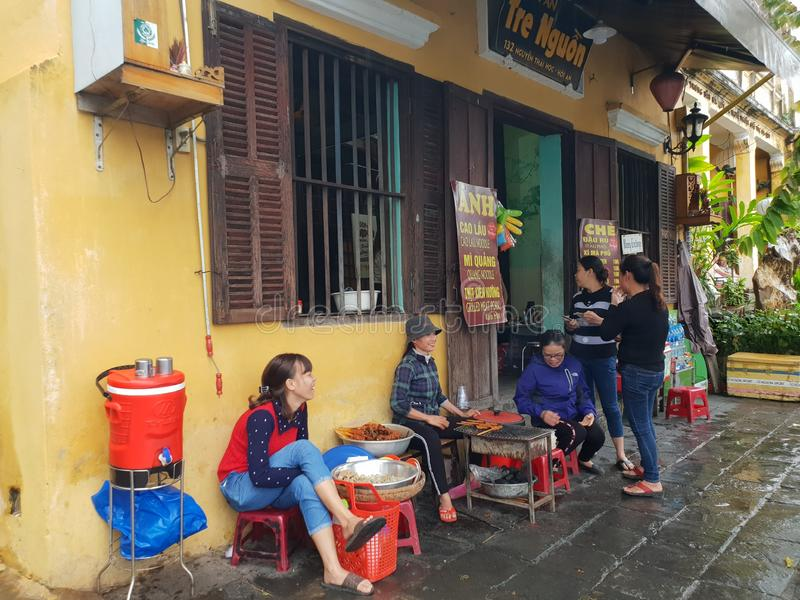 Vietnamese ladies chat in front of local food shop in Hoi an ancient street town in Vietnam. Vietnamese ladies chat in front of local food shop in Hoi an royalty free stock images