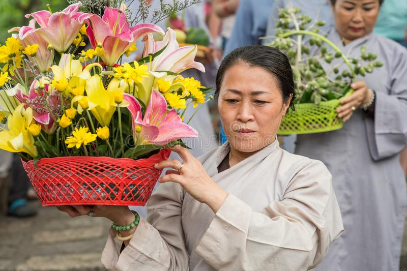 Vietnamese lady with a basket of flowers. Nha Trang, Vietnam - May 5, 2018: A woman with a basket of flowers in the procession of Po Nagar Temple festival Le hoi stock photography