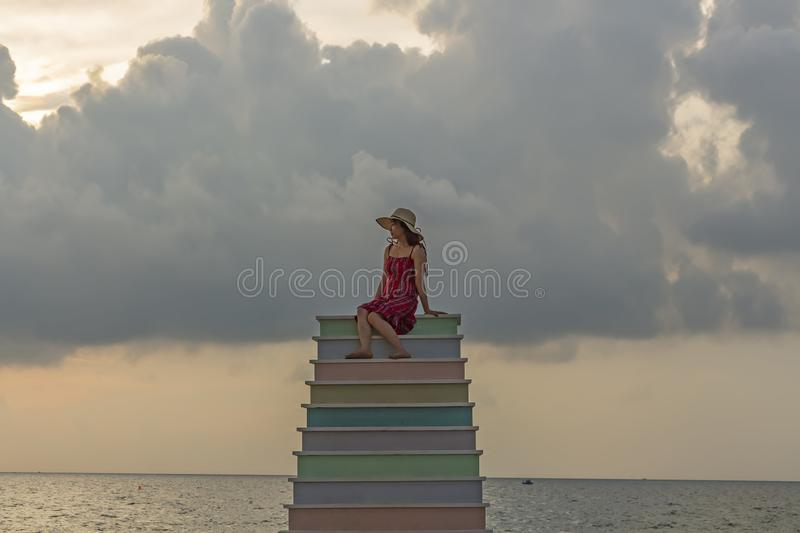 A vietnamese lady sitting on multicolored step structure at a beach stock image