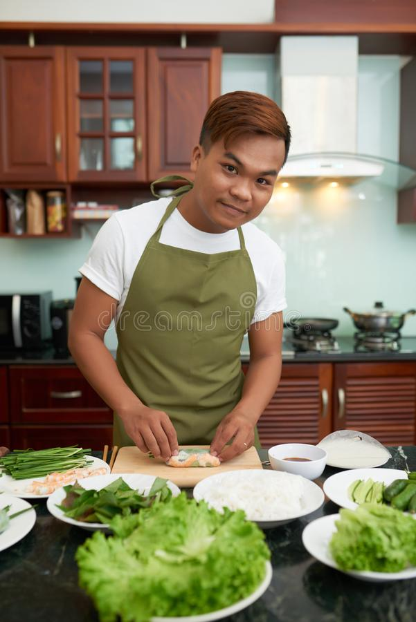 Vietnamese man ejoying cooking. Handsome young Vietnamese man cooking spring rolls with fresh ingredients at home royalty free stock photography