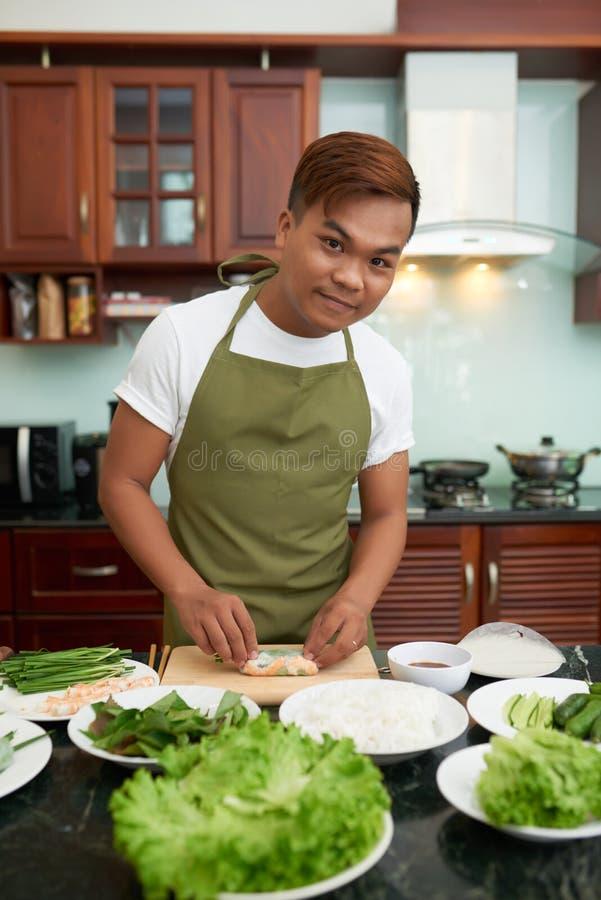 Vietnamese man ejoying cooking royalty free stock photography