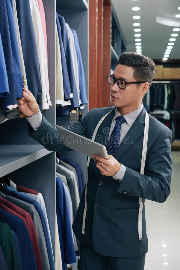 Menswear shop assistant. Vietnamese menswear shop assistant with digital tablet checking buttons on jackets on racks royalty free stock photography