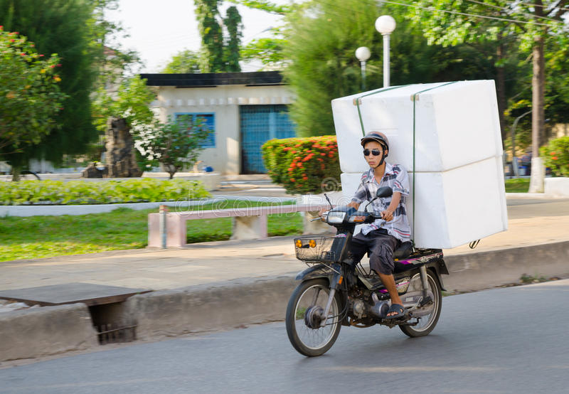 Vietnamese motorcyclist drives rectangular packages. PHAN THIET, VIETNAM - MARCH 5, 2015: An unidentified motorcyclist drives large foam plastic boxes. The main stock photo