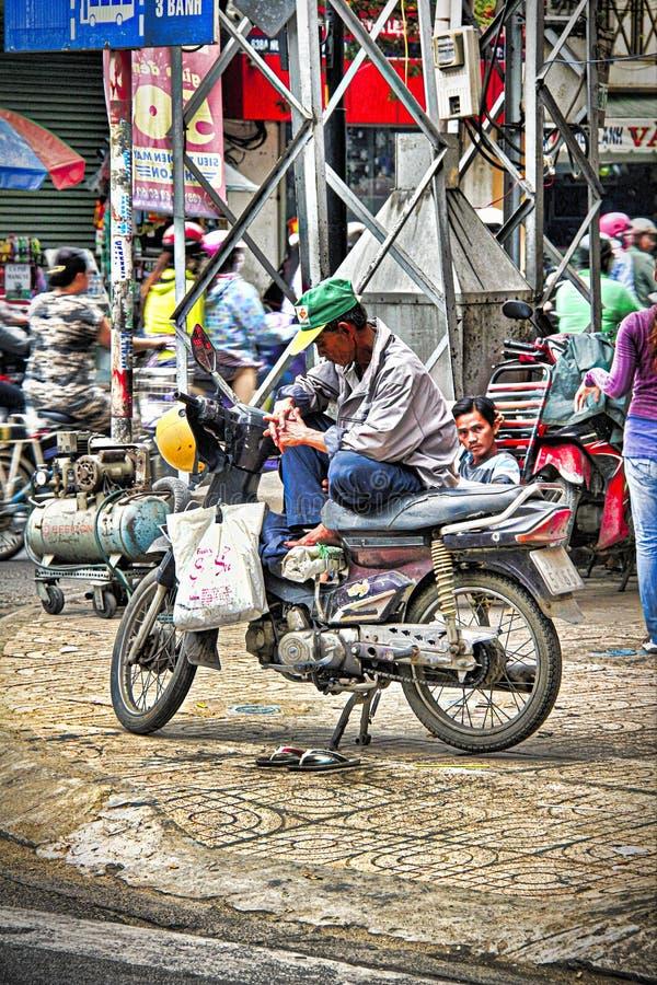 Vietnamese oude mensenzitting op een autoped stock foto