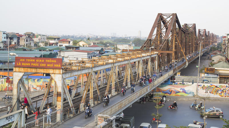 Vietnamese people riding motorcycles on Long Bien bridge. Hanoi, Vietnam - Feb 18, 2017: Vietnamese people riding motorcycles on Long Bien bridge over Hong Red royalty free stock photography