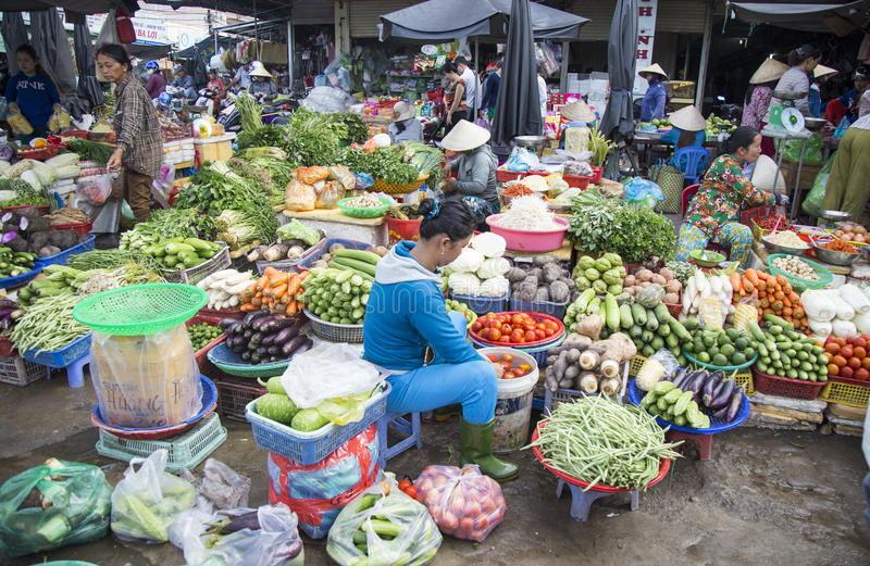 Vietnamese people selling vegetable and fruit. Phu Quoc, Vietnam - Mar 22, 2017: Vietnamese people selling vegetable and fruit at Duong center district market royalty free stock photo