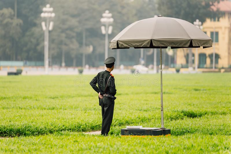 Vietnamese police officers standing under umbrella on the green field in front of Ho Chi Minh Mausoleum at Hanoi, Vietnam.  stock photo