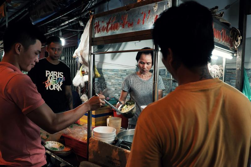 Vietnamese sale man cook noodle soup on food cart at night street food stock photo
