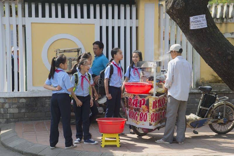 Vietnamese schoolgirls buy food from a street vendor during break. Hue, Vietnam. HUE, VIETNAM - JANUARY 08, 2016: Vietnamese schoolgirls buy food from a street royalty free stock photos