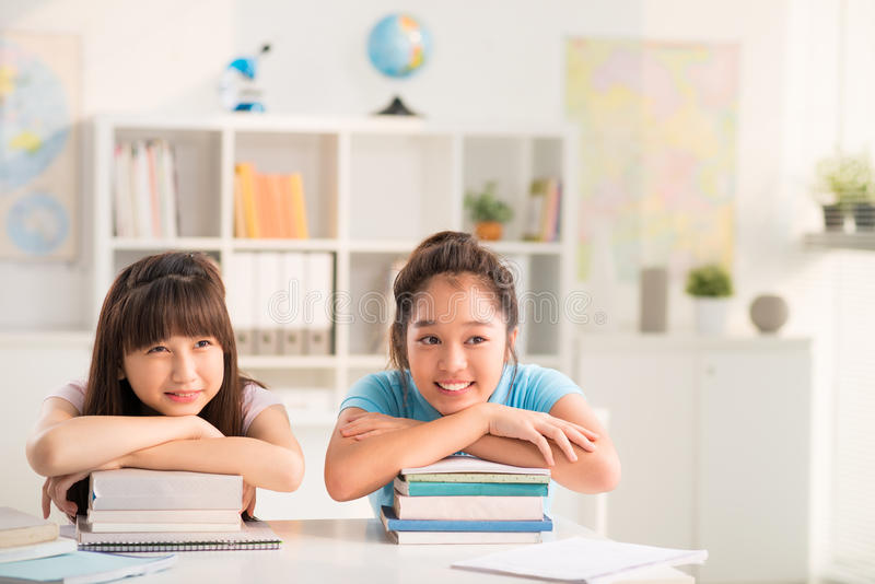Vietnamese schoolgirls. Two Vietnamese schoolgirls sitting at table and leaning on the stacks of book stock photo