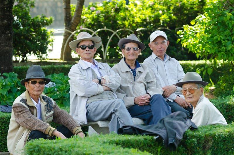 Vietnamese senior men rest in park stock photo