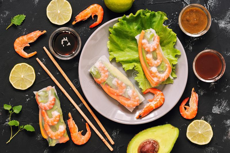 Vietnamese spring rolls with prawns, avocado, lettuce, sauces, chopsticks. Black concrete background, top view closeup. royalty free stock images