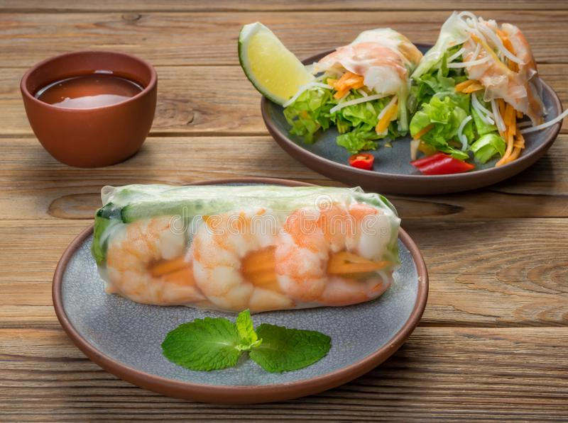 Vietnamese spring rolls with shrimps on two plates on wooden background. Soft focus. Close Up view of Vietnamese spring rolls with shrimps on two plates on stock photography