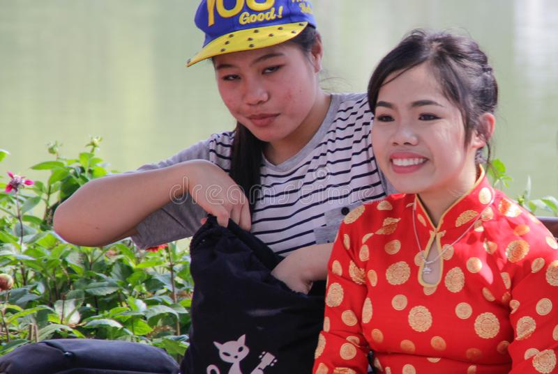 Vietnamese teenagers little girls in a traditional dress are sitting on a bench in the center of Hanoi. Hanoi, Vietnam - February 23, 2016: Vietnamese teenagers stock images