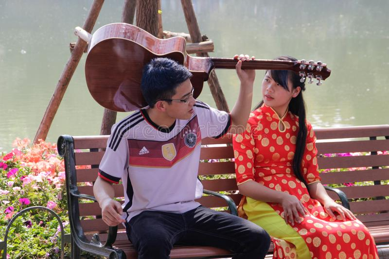 Vietnamese teens couple in love girl in a traditional dress are sitting on a bench with a guitar royalty free stock photo