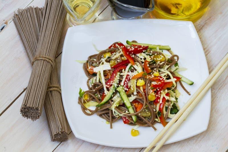 Vietnamese vegetarische salade met boekweitnoedels, wortelenkomkommers, Spaanse peper en sesamzaden, macro op een plaat stock afbeelding